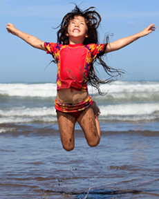 girl in red swimsuit jumping with arms out stretched as waves crash on surf behind her